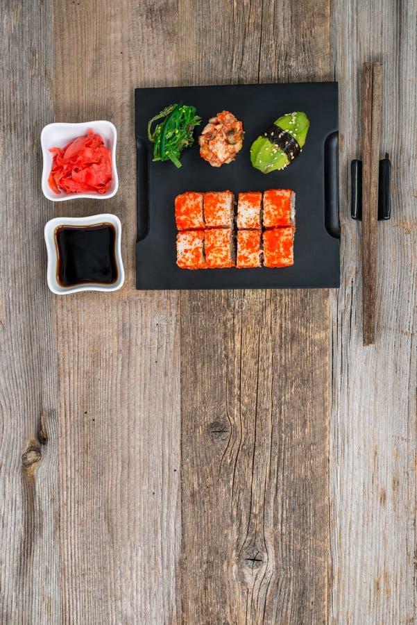 Grupo de sushi e de rolos com os hashis na tabela de madeira imagens de stock royalty free