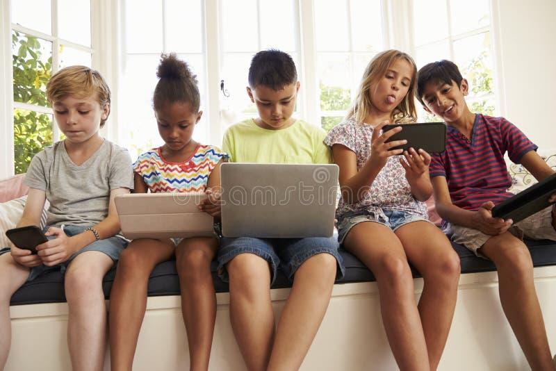 Grupo de tecnología del uso de Sit On Window Seat And de los niños imagen de archivo