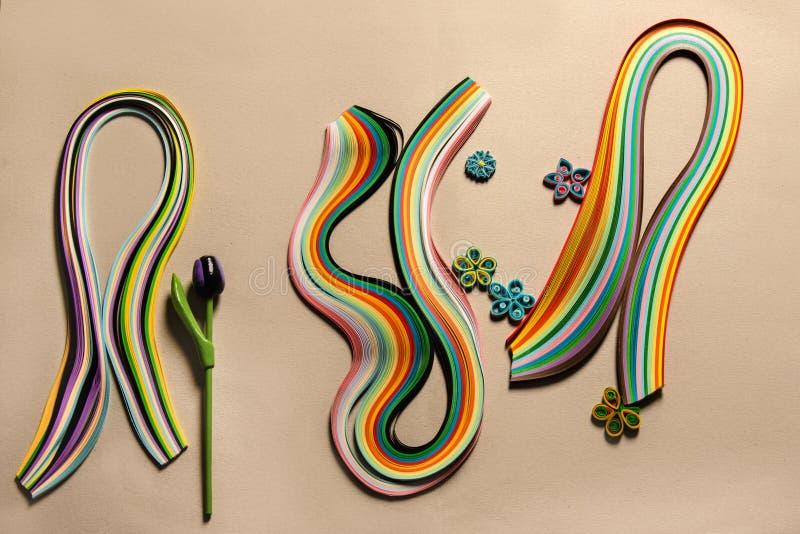 grupo de tiras de cor para quilling com uma amostra das flores de papel esta técnica fotografia de stock royalty free