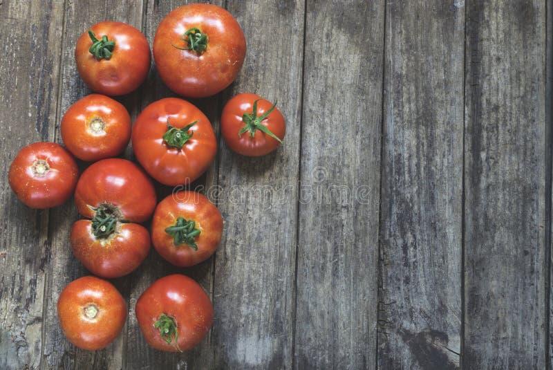 Grupo de tomates frescos, rojos en la tabla de madera vieja con el espacio de la copia foto de archivo libre de regalías