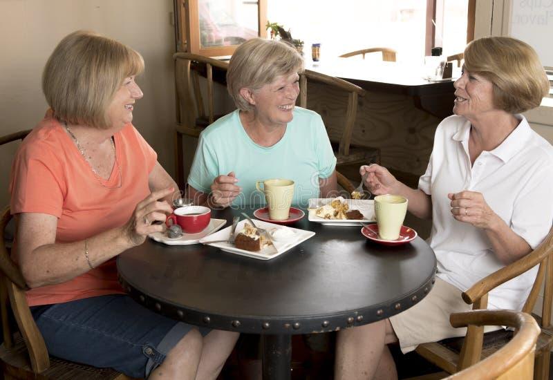Grupo de três amigas maduras superiores das mulheres da Idade Média bonita que encontram-se para o café e o chá com os bolos na c imagens de stock royalty free