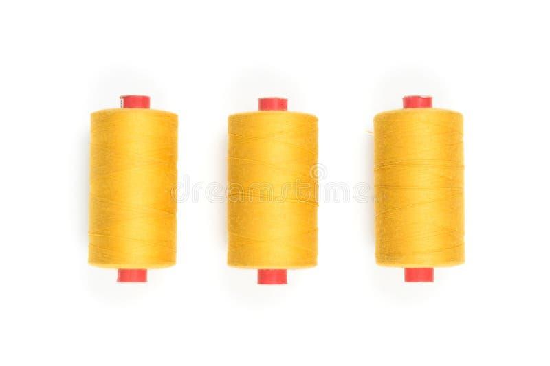 Grupo de três bobinas coloridas da linha no fundo, na costura e na costura brancos fotos de stock