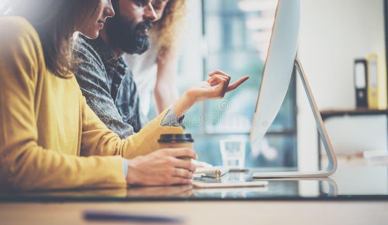 Grupo de três colegas de trabalho novos que trabalham junto em um escritório ensolarado Homem que datilografa no teclado de compu fotografia de stock royalty free