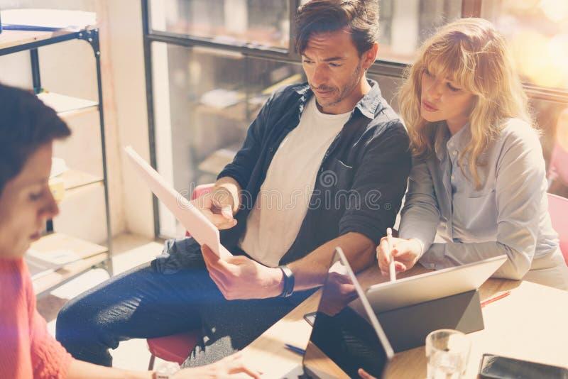 Grupo de três colegas de trabalho novos que trabalham no laptop no escritório ensolarado Mulher que guarda os originais de papel  fotos de stock