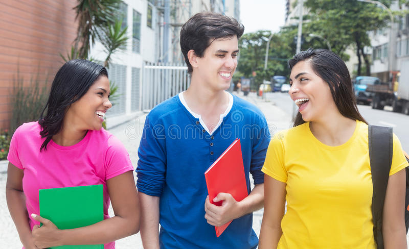 Grupo de três estudantes internacionais que andam na cidade imagens de stock royalty free