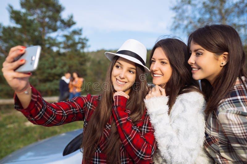 Grupo de três jovens mulheres que viajam junto imagens de stock