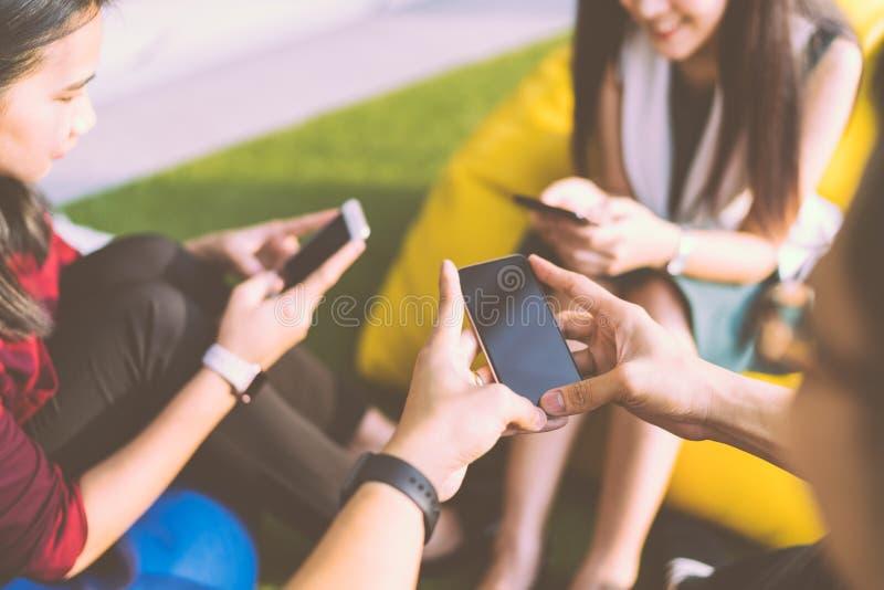 Grupo de três jovens que usam smartphones junto, o estilo de vida ou o conceito moderno do dispositivo da tecnologia de comunicaç fotos de stock