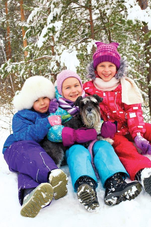 Grupo de três meninas das crianças que sentam-se na neve junto fotos de stock royalty free