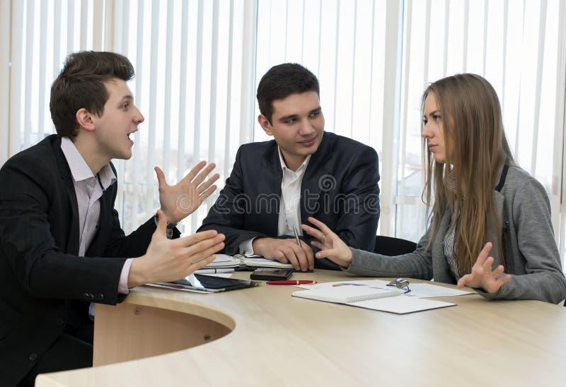 Grupo de três povos que têm a discussão imagens de stock royalty free