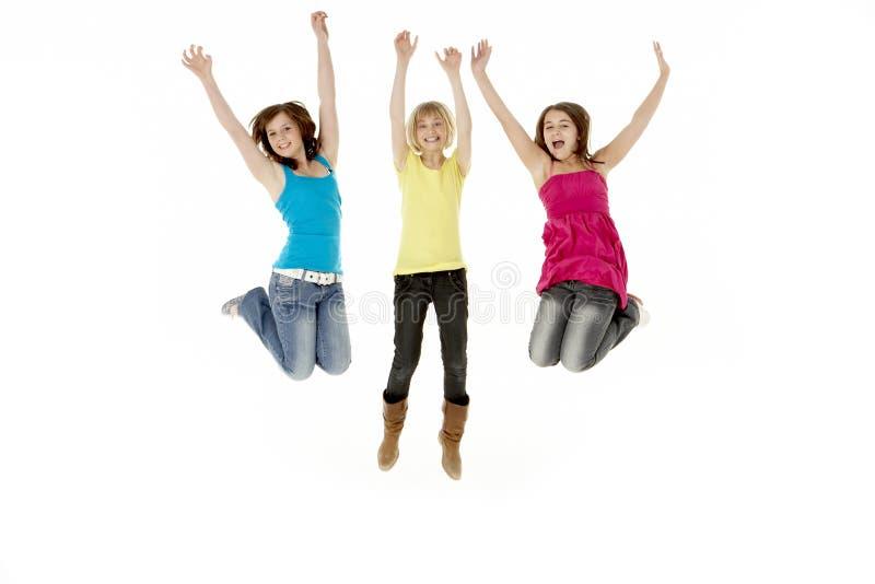 Grupo de três raparigas que pulam no ar foto de stock