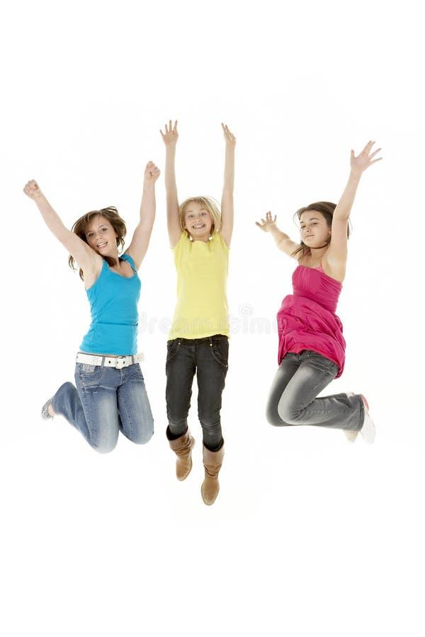 Grupo de três raparigas que pulam no ar fotos de stock