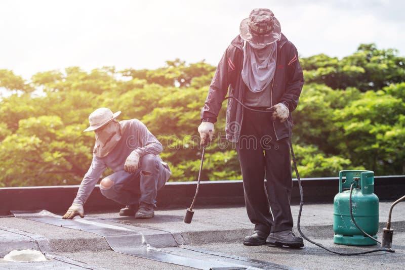 Grupo de trabajador que instala la hoja del alquitrán en el tejado del edificio imágenes de archivo libres de regalías