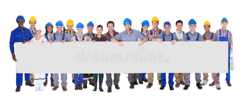 Grupo de trabajadores de construcción con el cartel imagen de archivo