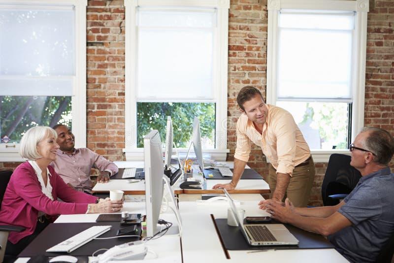 Grupo de trabajadores en los escritorios en oficina conceptora moderna imagenes de archivo