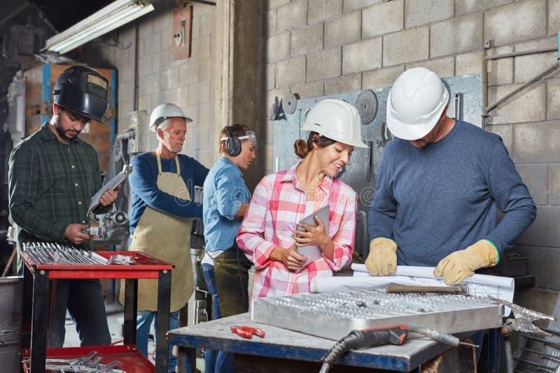 Grupo de trabajadores en taller imagen de archivo libre de regalías