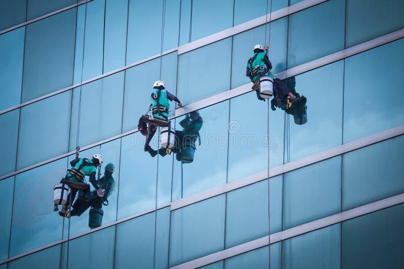 Grupo de trabajadores que limpian servicio de las ventanas en el alto edificio de la subida fotografía de archivo