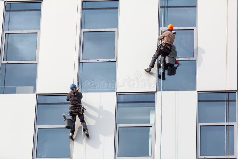 Grupo de trabajadores que limpian servicio de las ventanas en alta subida foto de archivo libre de regalías