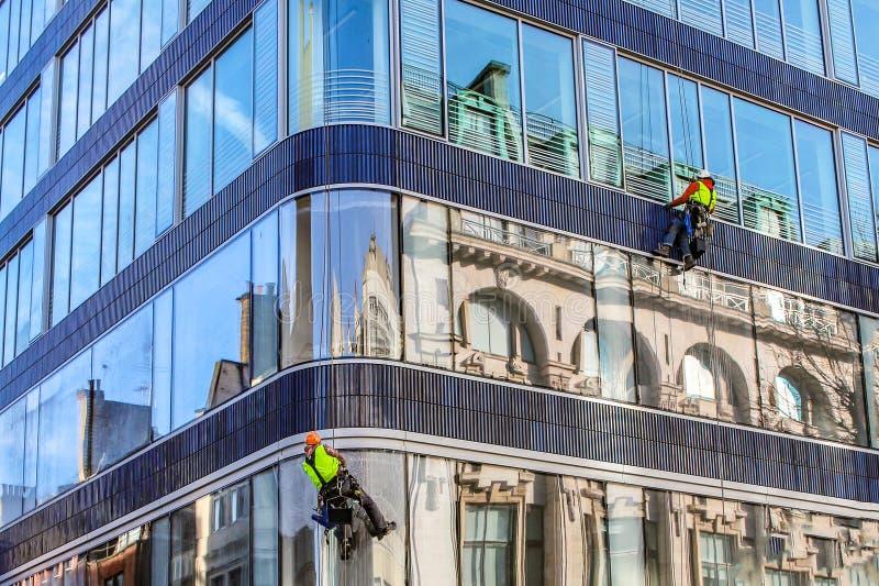 Grupo de trabajadores que limpian servicio de las ventanas en el alto edificio de la subida fotos de archivo