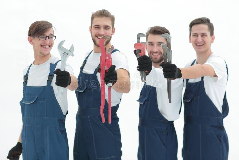 Grupo de trabalhadores da construção com ferramentas de funcionamento imagens de stock