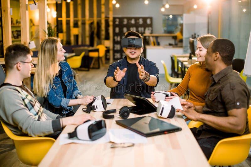 Grupo de trabalhadores do empregado dos jovens que têm o divertimento com os óculos de proteção da realidade virtual do vr no est imagem de stock