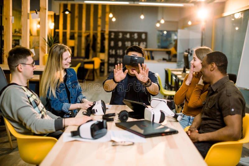 Grupo de trabalhadores do empregado dos jovens que têm o divertimento com os óculos de proteção da realidade virtual do vr no est foto de stock royalty free