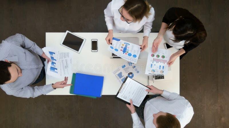 Grupo de trabalhadores de escritório que discutem diagramas e gráficos do negócio foto de stock