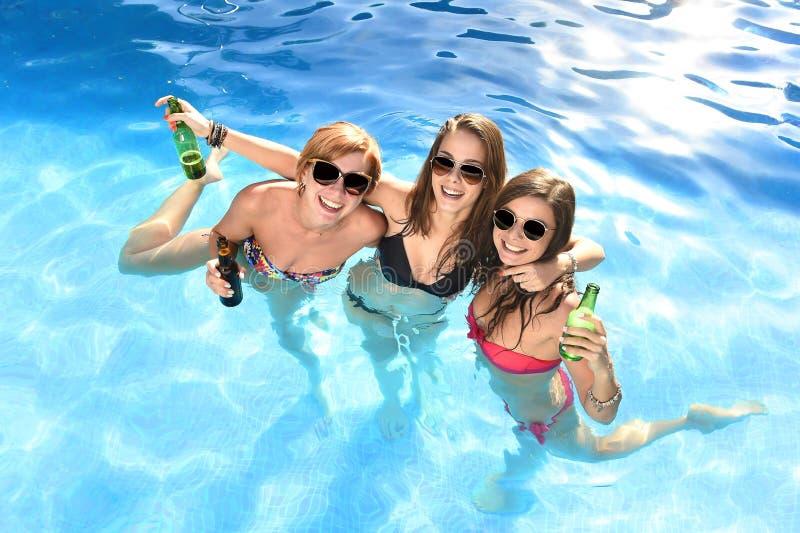 Grupo de tres amigas felices que tienen baño en la piscina t imagen de archivo