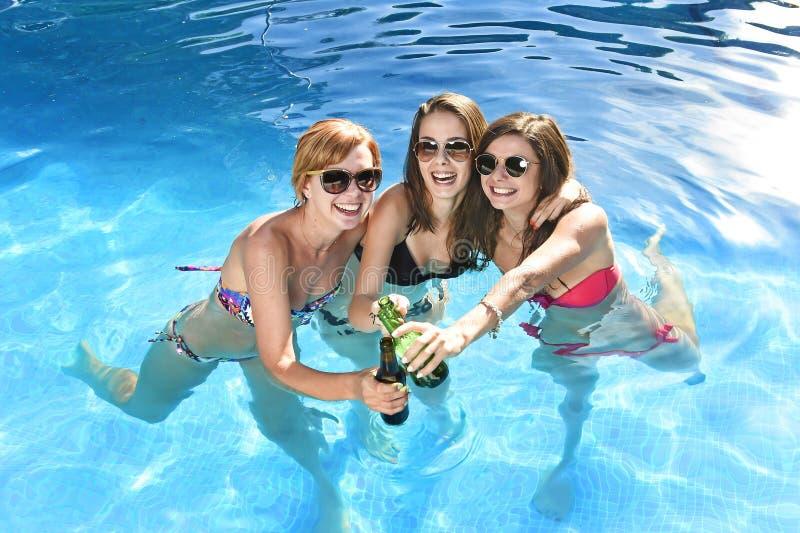 Grupo de tres amigas felices que tienen baño en la piscina t fotos de archivo