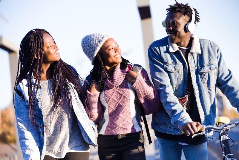 Grupo de tres amigos que caminan y que ríen en la calle foto de archivo libre de regalías