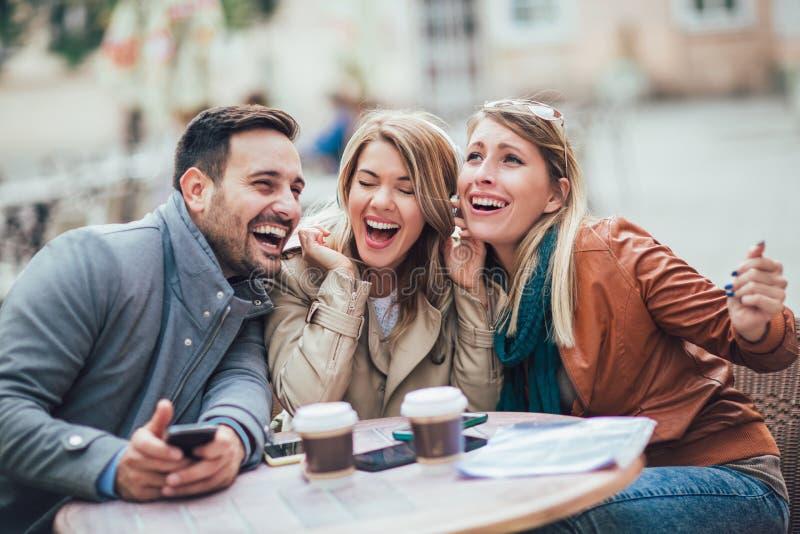 Grupo de tres amigos que usan el teléfono en café al aire libre foto de archivo