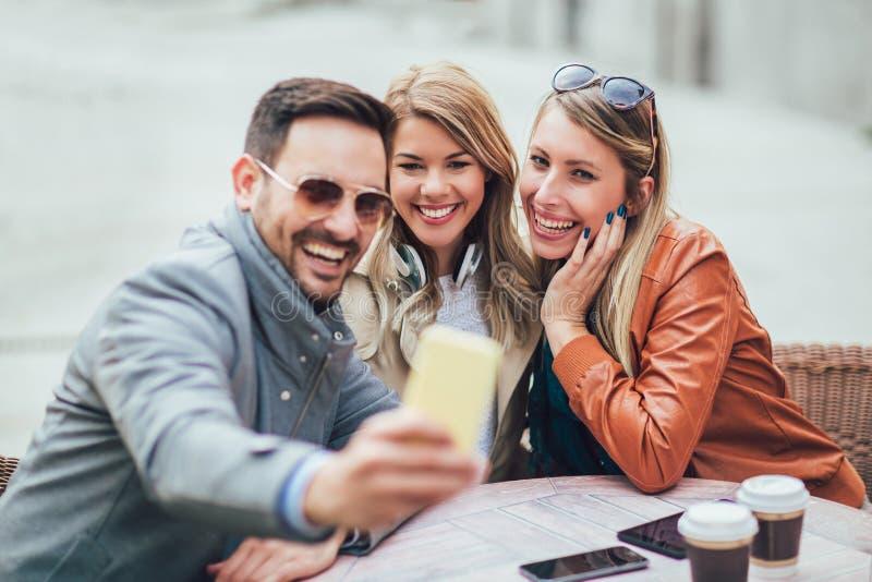 Grupo de tres amigos que usan el teléfono en café al aire libre fotos de archivo libres de regalías