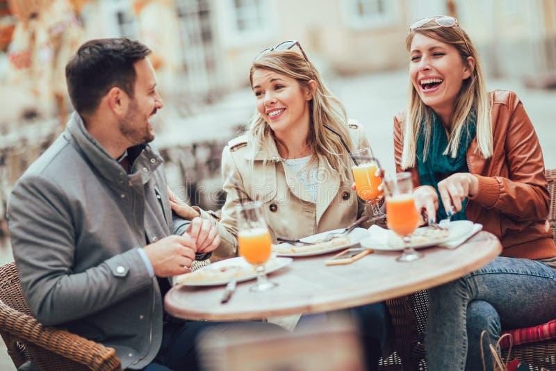 Grupo de tres amigos que usan el teléfono en café al aire libre el día soleado fotos de archivo libres de regalías