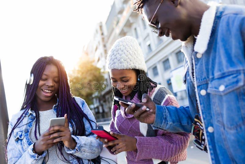 Grupo de tres amigos que usan el teléfono móvil en la calle imagen de archivo libre de regalías