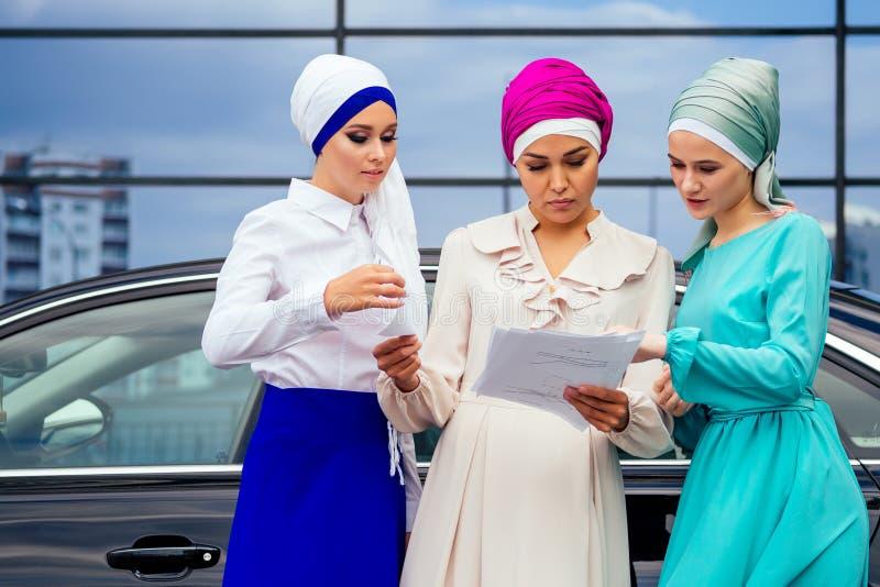 Grupo de tres exitosas estudiantes de negocios musulmanas mujeres con un elegante hiyab con velo y un velo turbante atado foto de archivo