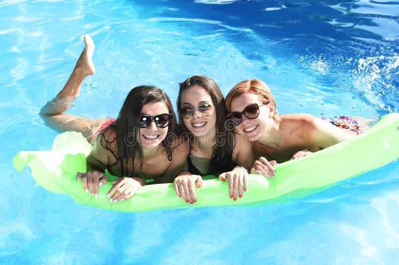 Grupo de tres felices y amigos de chica joven hermosos que tienen palo fotos de archivo