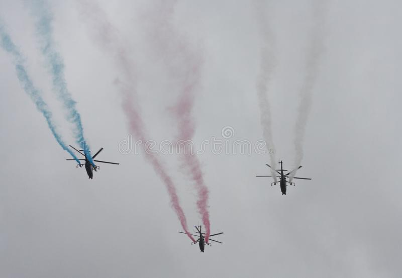 Grupo de tres helic?pteros con humo del color en el cielo en desfile militar fotos de archivo