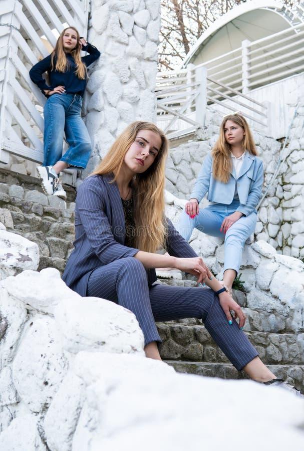Grupo de tres muchachas agradables elegantes jovenes en los trajes del pantsuit que sientan en las escaleras cerca de la construc foto de archivo libre de regalías