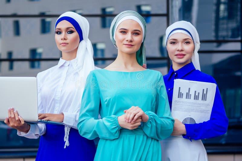 Grupo de tres mujeres empresarias musulmanas caucásicas con un elegante hiyab y turbante trabajando en la calle fotos de archivo