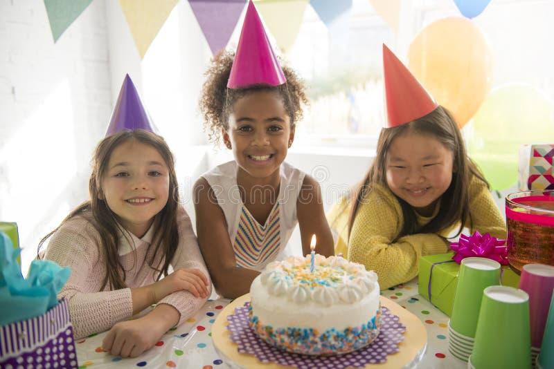 Grupo de tres niños adorables que se divierten en la fiesta de cumpleaños fotos de archivo libres de regalías