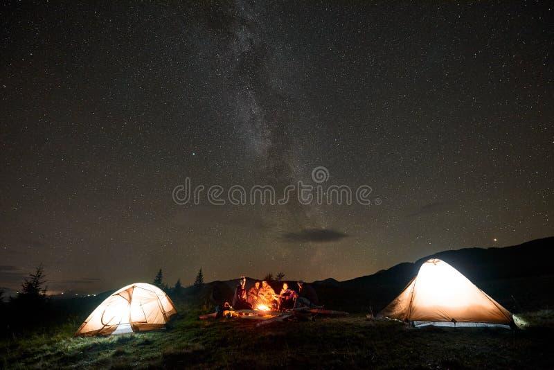 Grupo de turistas con la guitarra quemando la hoguera debajo del cielo estrellado oscuro con la constelación de la vía láctea imágenes de archivo libres de regalías