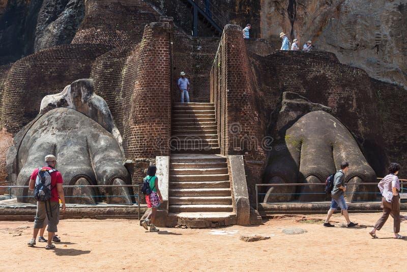 Grupo de turistas delante de la pata del león en el complejo de Sigiriya foto de archivo libre de regalías