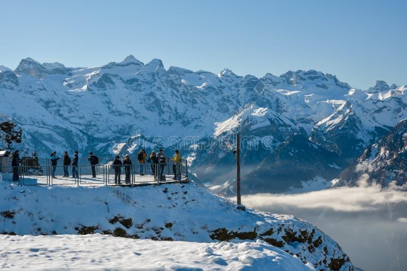 Grupo de turistas e de esquiadores sobre Fronalpstock perto de Stoos imagem de stock