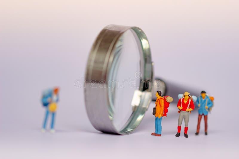 Grupo de turistas e de lente de aumento isolados no fundo branco Conceitos de viagem imagem de stock