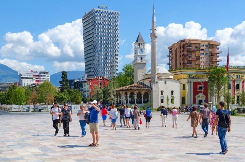 Grupo de turistas en el cuadrado de Skanderbeg Efem Bey Mosque, torre de reloj, hotel de la plaza, Tirana, Albania imagen de archivo libre de regalías