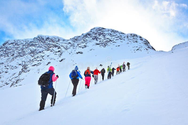Grupo de turistas a escalar em uma passagem de montanha nevado imagens de stock