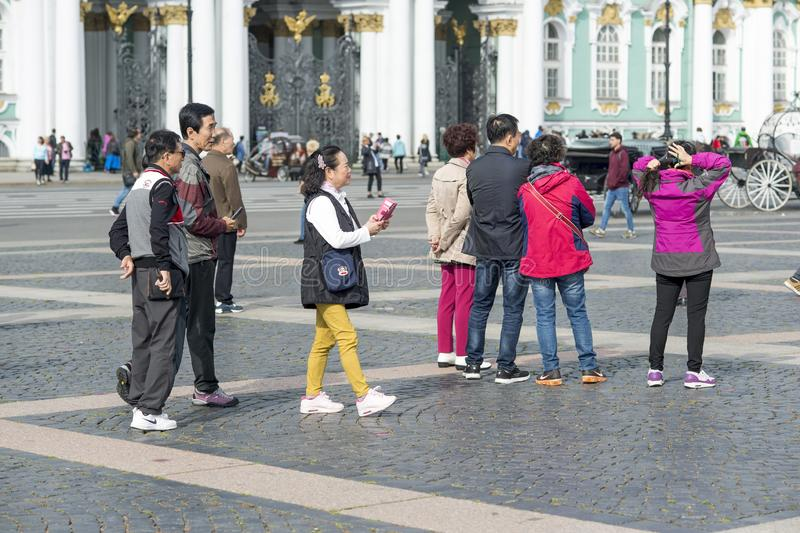 Grupo de turistas orientales del aspecto asiático en el cuadrado del palacio de St Petersburg en el fondo de la ermita, Rusia, imágenes de archivo libres de regalías