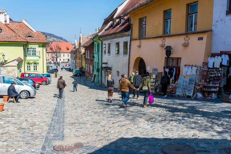 Grupo de turistas que admiram as ruas medievais coloridas, lojas de lembranças na parte dianteira das casas fotografia de stock royalty free