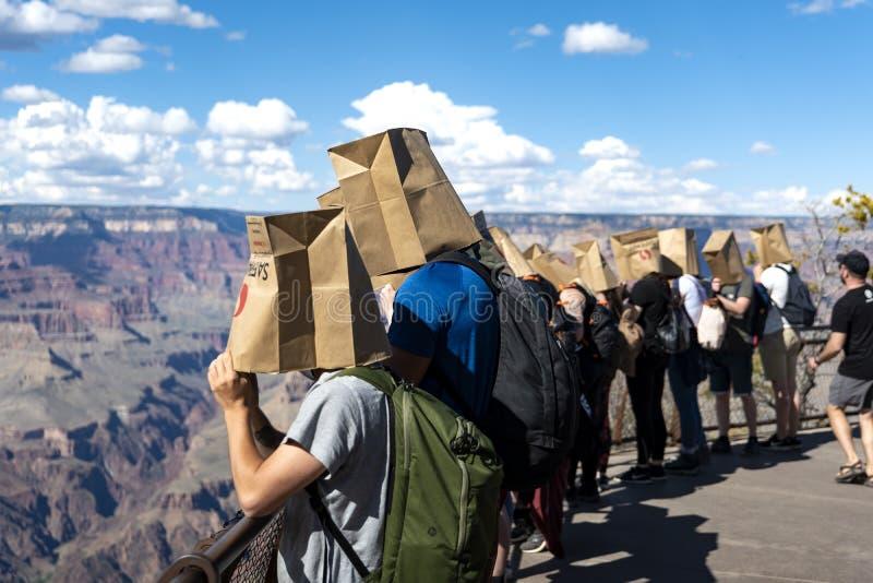Grupo de turistas que llevan las bolsas de papel en sus cabezas imágenes de archivo libres de regalías