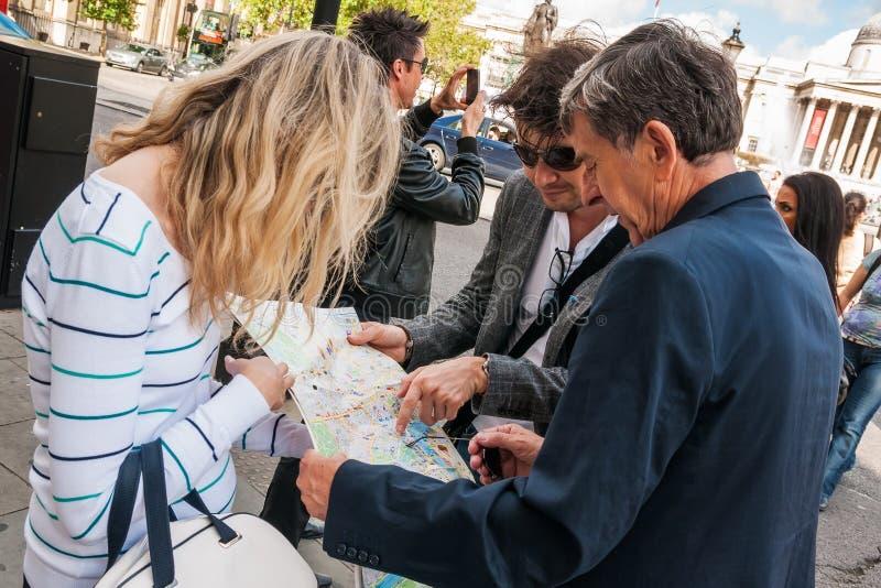 Grupo de turistas que se colocan en Trafalgar Square y que miran el mapa foto de archivo