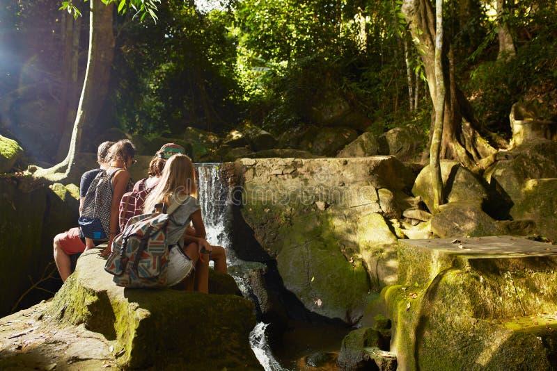 Grupo de turistas que se sientan en las rocas que miran la cascada en Tailandia fotos de archivo libres de regalías